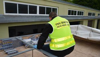 W kontrolowanym busie ujawniono podwójny dach, w którym ukryto 26 tys. paczek papierosów / fot. NOSG