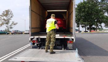 Funkcjonariusz straży granicznej przy skradzionych samochodach / fot. NOSG